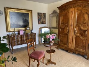 intérieur de la boutique avec un guéridon en noyer et une chaise directoire en velours rose Chez l'Antiquaire